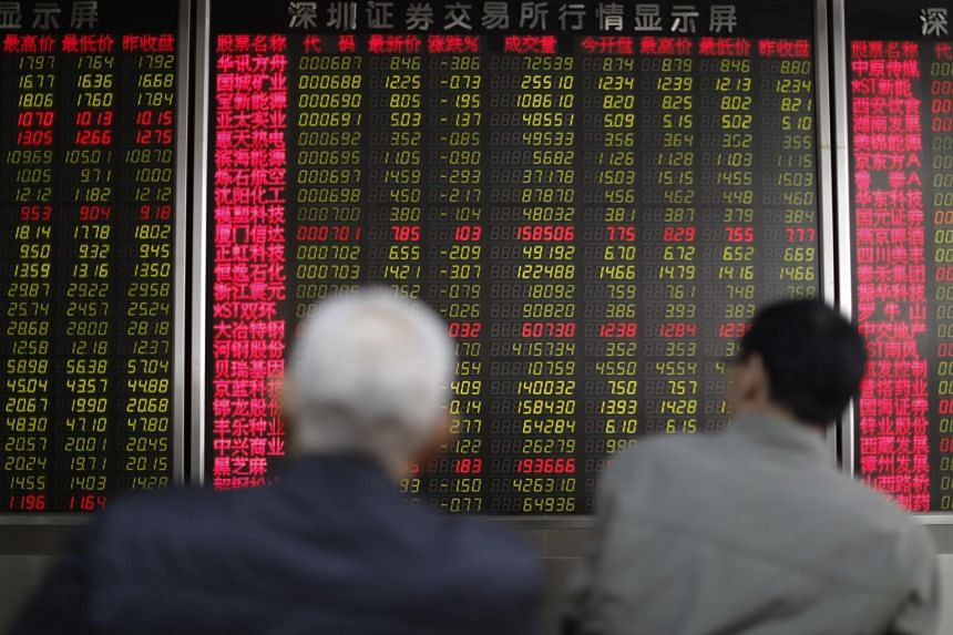 Chinese investors watch an electronic board showing the stock prices at a securities brokerage house in Beijing, China, on March 20, 2019.