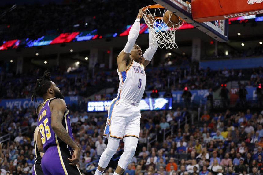 Oklahoma City Thunder guard Russell Westbrook (right) dunks the ball as Los Angeles Lakers guard Reggie Bullock looks on during the second half at Chesapeake Energy Arena.
