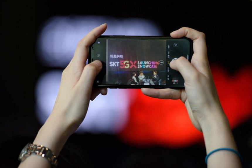 An audience member takes a photo during an SK Telecom launch event for the company's 5G mobile network, in Seoul on April 3, 2019.