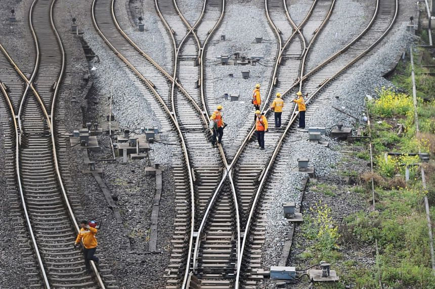 Workers inspect railway tracks, which serve as a part of the Belt and Road freight rail route linking Chongqing to Duisburg, on March 14, 2019.