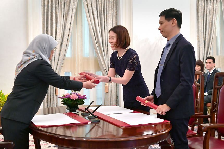 President Halimah Yacob handing letters of appointment to Ms Lai Wei Lin and Mr Joseph Leong Weng Keong at the Istana as they were sworn into their new roles in the Government yesterday. Mr Leong was appointed Permanent Secretary (Defence Development