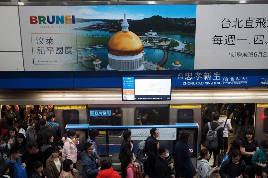 """Passengers walk near a Royal Brunei Airlines billboard promoting Brunei as an """"abode of peace"""" at a mass rapid transit system station in Taipei, Taiwan."""