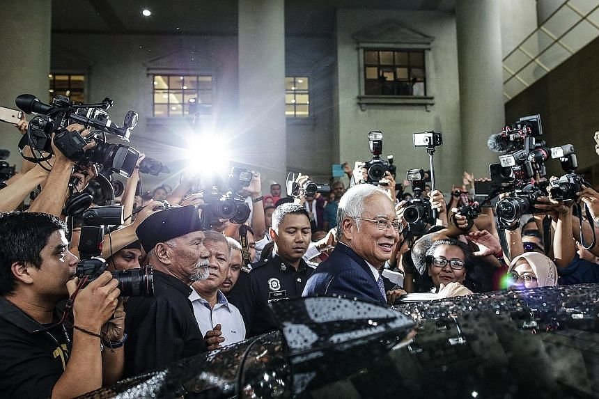Former Malaysian premier Najib Razak (centre) leaving the Kuala Lumpur High Court yesterday. In this trial, Najib faces three counts of criminal breach of trust, one charge of abuse of power and three counts of money laundering involving funds from S
