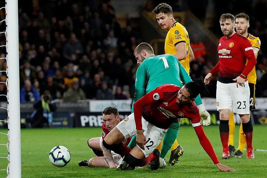 Manchester United defender Chris Smalling (No. 12) scoring an own goal that gave Wolves a 2-1 Premier League win at the Molineux on Tuesday. It was United's second loss to the same team in three weeks.