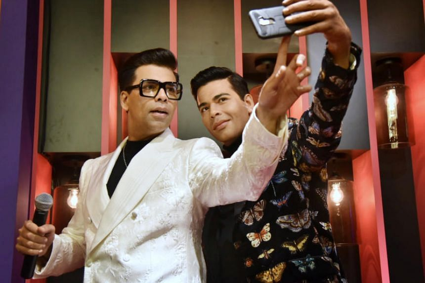 Indian film-maker Karan Johar with his wax figure at Madame Tussauds Singapore's new Ultimate Film Star Experience zone.