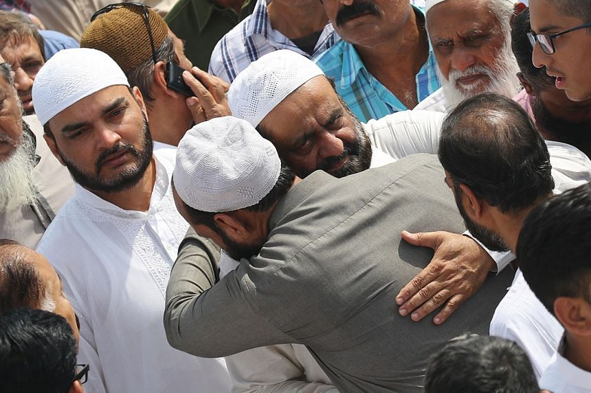 Relatives and friends hug the father (centre) of Syed Areeb Ahmed, one of the nine Pakistani victims of the mass shooting in Christchurch, after his body was taken to Pakistan..