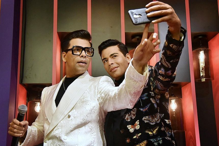 Indian film-maker Karan Johar (far left) was in Singapore for the unveiling of his wax figure (left) at Madame Tussauds Singapore's new Ultimate Film Star Experience zone.