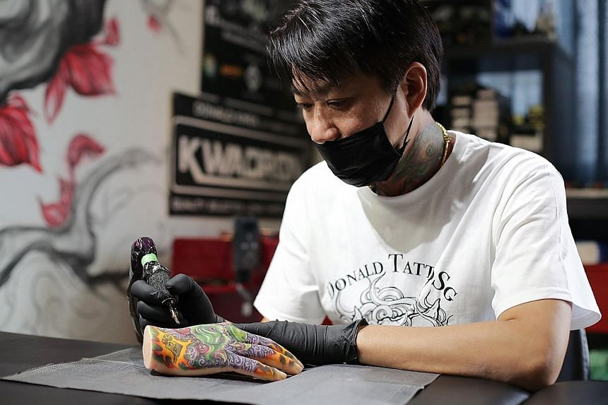 Tattoo artist Donald Kwek (left) specialises in customised Oriental designs while Mr Jon Lim (above) is known for illustrative blackwork (right) - a tattoo style with designs characterised by bold, black shading.
