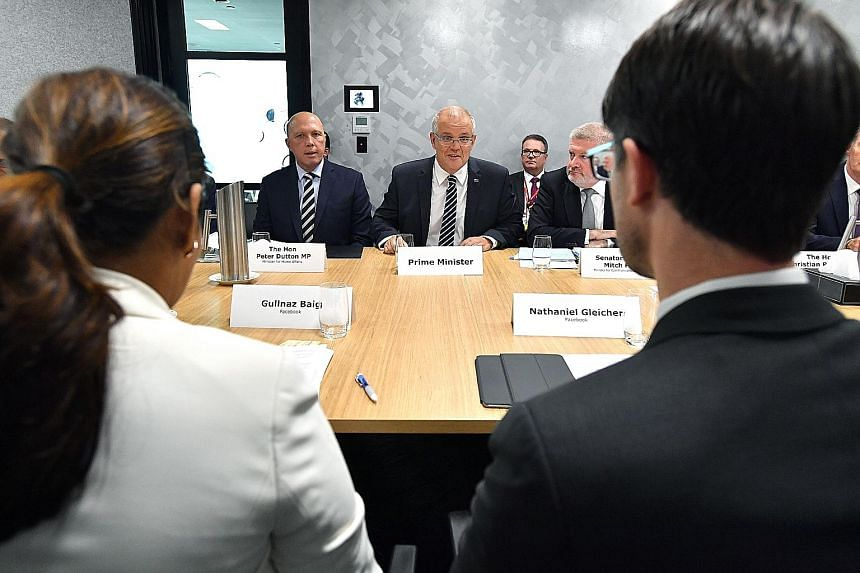 Australian Prime Minister Scott Morrison (centre) and Home Affairs Minister Peter Dutton (on his right) speaking with Facebook executives at a meeting with social media executives in Brisbane last week. The new law has angered technology firms, which