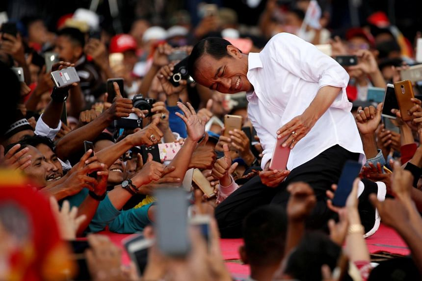 President Joko Widodo takes pictures with his supporters during his first campaign rally at a stadium in Serang, Banten province, Indonesia, on March 24, 2019.