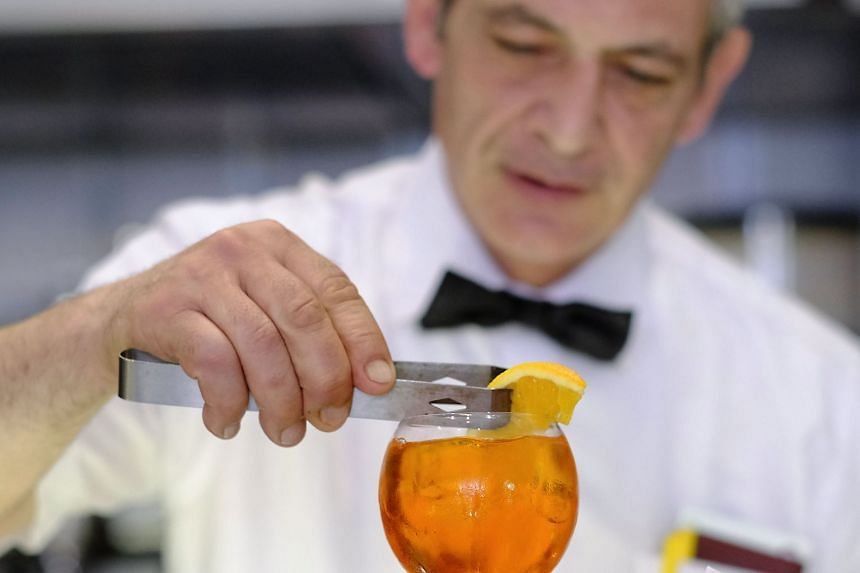 A bartender prepares a cocktail at a cafe in central Rome.