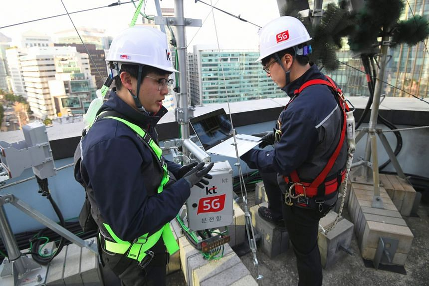 Technicians with South Korean telecom operator KT checking an antenna for the 5G mobile network service on the rooftop of a building in Seoul yesterday. Three South Korean mobile carriers and US telco Verizon launched 5G services on Wednesday ahead o