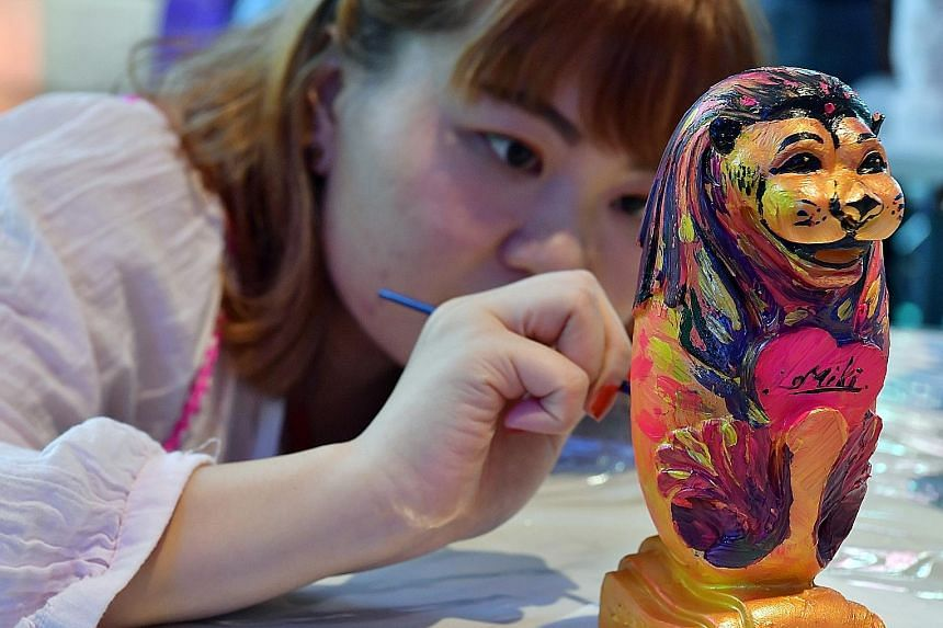 Graphic designer Lim Mei Kee, 27, painting a 20cm-tall miniature Merlion at a workshop organised under the first Lion's Pride event at Orchard Gateway. Each mini Merlion costs $38 for members of the public. There is also a 1.6m-tall Merlion in the ma