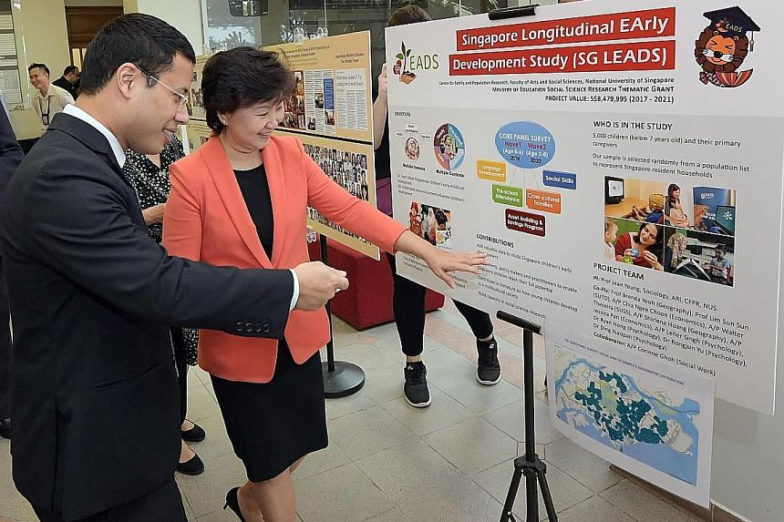 Professor Wei-Jun Jean Yeung, co-director of the Centre for Family and Population Research, and Minister for Social and Family Development Desmond Lee viewing an exhibit featuring the Singapore Longitudinal Early Development Study.