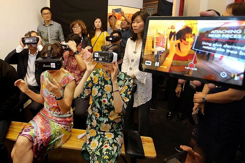 Above: The revamped Stamford Arts Centre. Right: Minister for Culture, Community and Youth Grace Fu (seated on left) trying out the Chinese opera VR stage tour yesterday with National Arts Council chairman Chan Heng Chee (seated on right), as NAC chi