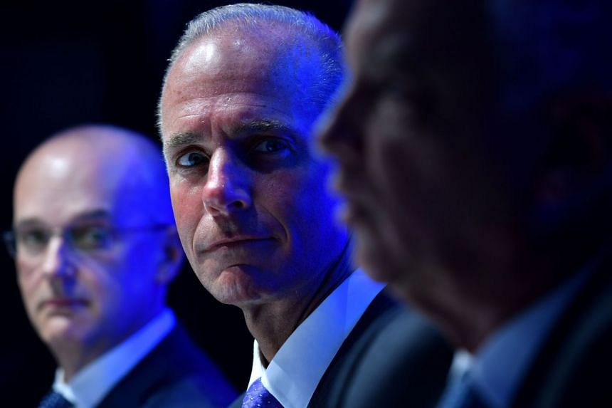 Boeing CEO Dennis Muilenburg (centre, in a file photo) described the production cut as temporary..