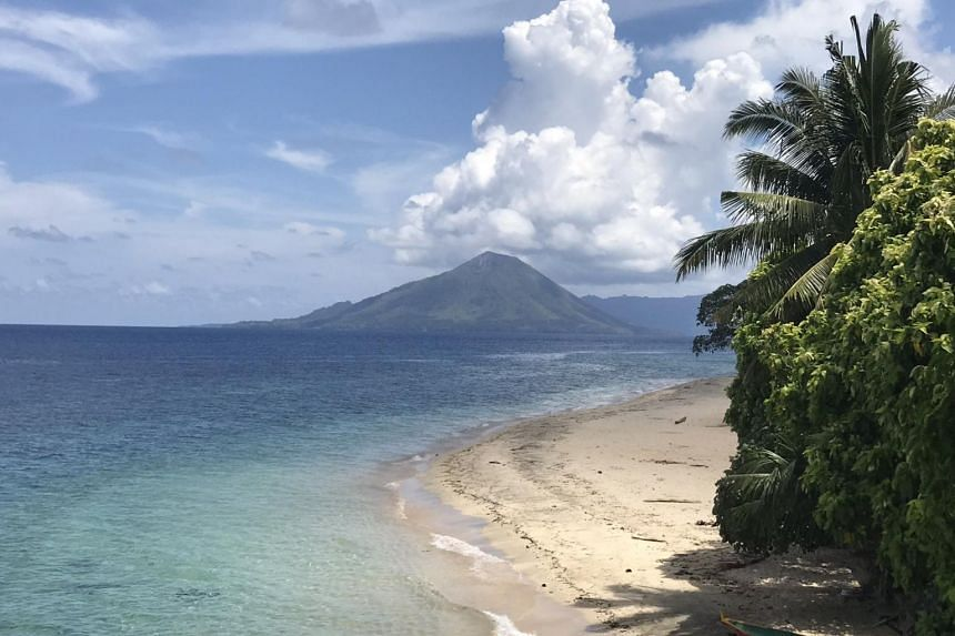 The classic cone of Banda Api, one of the active volcanoes in the Banda Islands, seen from the idyllic shores of neighbouring Pulau Ai.