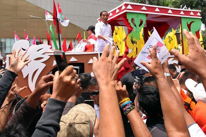 Incumbent Indonesian president Joko Widodo (centre) greets his supporters during a political campaign rally in Palembang, South Sumatra, on April 2, 2019.