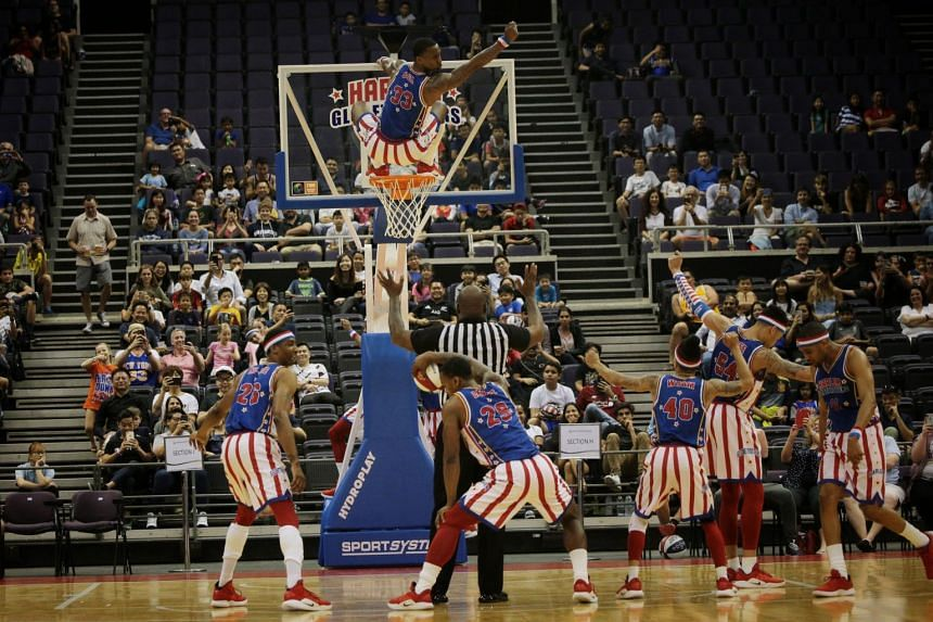 "The Harlem Globetrotters' William ""Bull"" Bullard (33) perching atop the basketball hoop, as his teammates dance during their exhibition match at the Singapore Indoor Stadium last night."