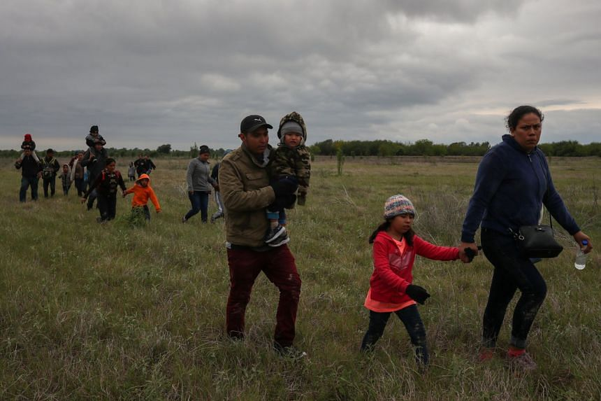 Asylum-seeking migrant families from Central America walk through a field to the main road after they illegally crossed the Rio Grande river into the US from Mexico.