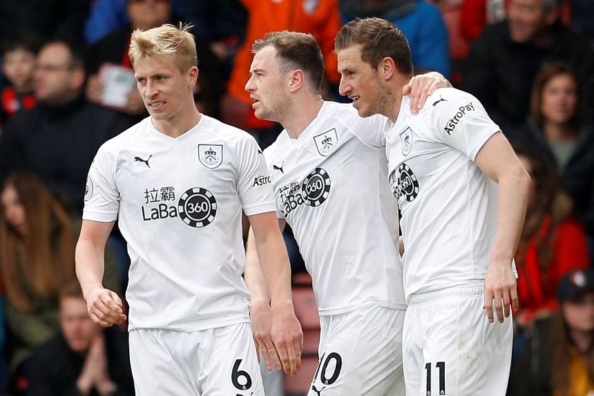 Burnley's Ashley Barnes celebrates scoring their third goal with Ben Mee and Chris Wood.
