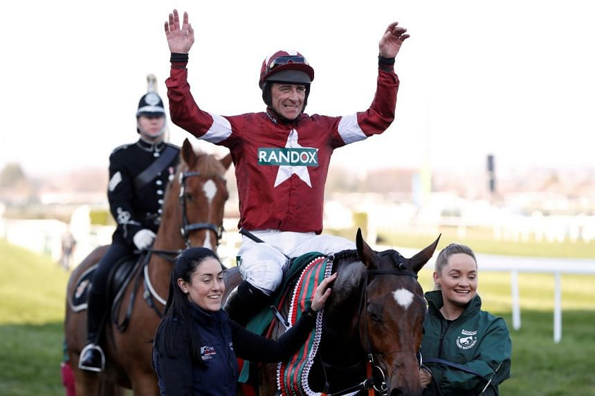 Davy Russell celebrates on Tiger Roll after winning the race.