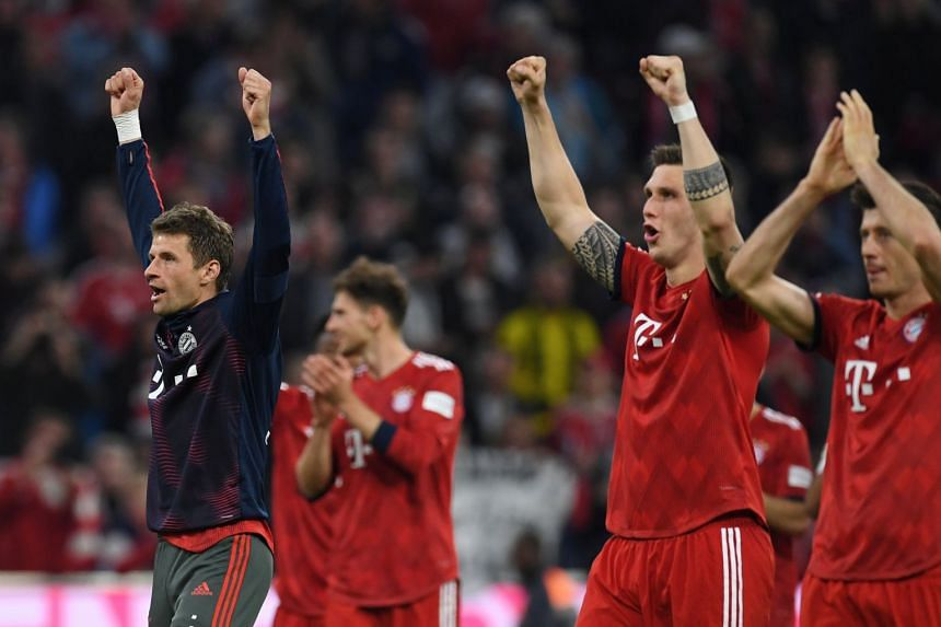 Bayern Munich's Thomas Mueller celebrates after the match with team mates.