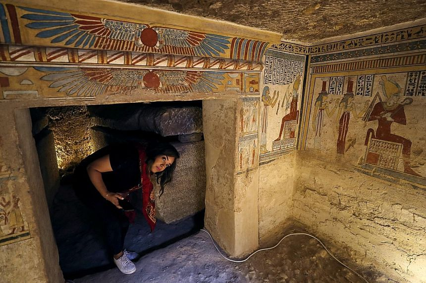 An archaeologist holding an ancient mummified bird (above), found inside the tomb, which dates back more than 2,000 years. Also discovered were mummified mice and falcons (left). A tourist surrounded by paintings inside the newly discovered burial si