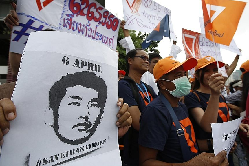 Supporters of Future Forward Party leader Thanathorn Juangroongruangkit waiting outside the Pathumwan police station in Bangkok yesterday. Thanathorn faces sedition charges by the National Council for Peace and Order alleging that he helped anti-coup