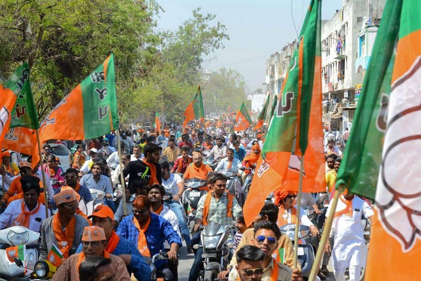 Indian Bharatiya Janta Party (BJP) supporters gather to follow BJP National President Amit Shah during his road show in Ahmedabad, on April 6, 2019.