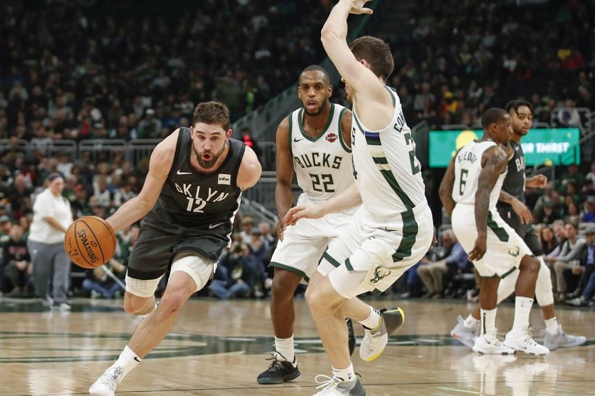 Brooklyn Nets forward Joe Harris (left) driving to the basket against Milwaukee Bucks forward Khris Middleton (centre) and guard Pat Connaughton (right) during their NBA match on April 6, 2019.
