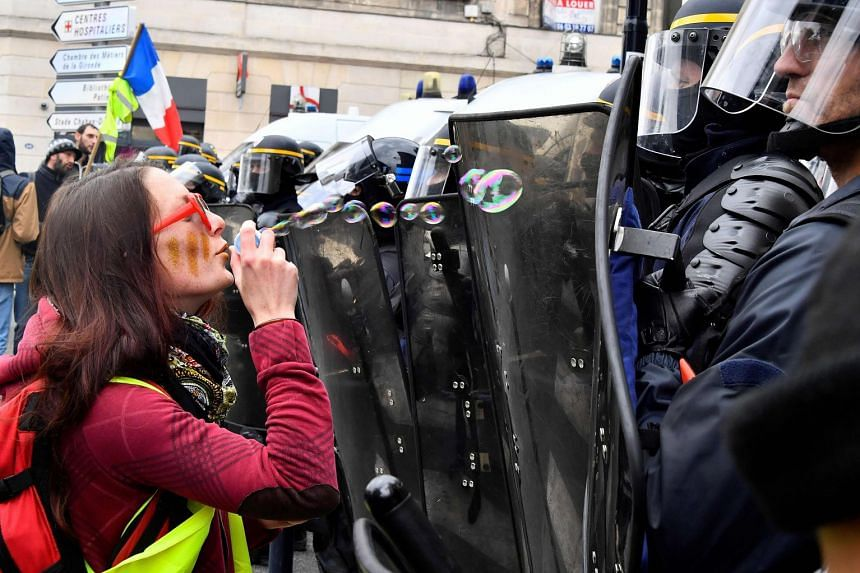A woman blows bubbles in front of riot police during a yellow vest protest in Bordeaux.