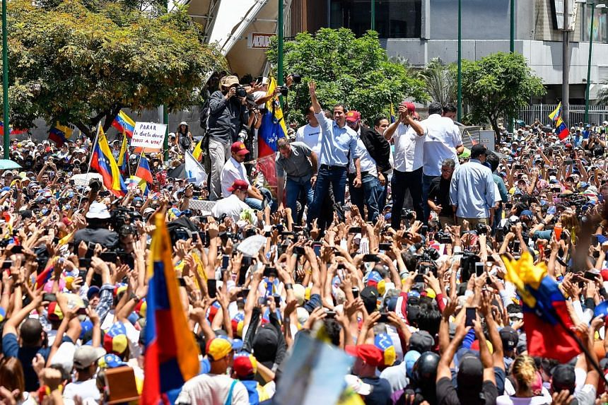 Juan Guaido (centre) waves to supporters during a demo at El Marques neighborhood in Caracas.