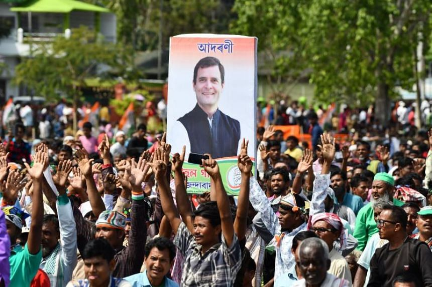 Congress party supporters carrying a poster of Indian National Congress party president Rahul Gandhi, during an election rally in Bokakhat, Assam state, on April 3, 2019.
