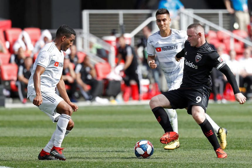 D.C. United forward Wayne Rooney (right) dribbling the ball against Los Angeles FC defender Eddie Segura (left) during their MLS match on April 6, 2019.