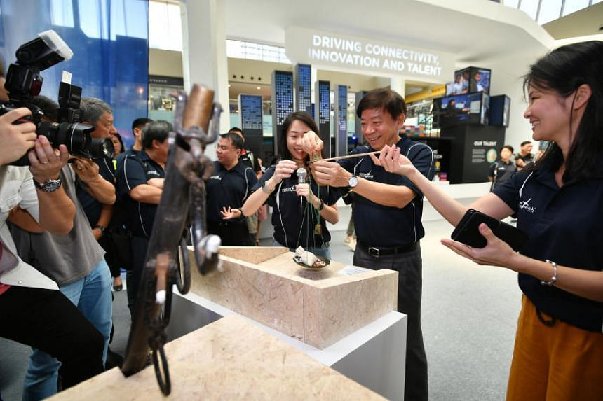 Mr Khaw Boon Wan trying out a user-friendly size daching, used to weigh herbs and other fine ingredients in traditional Chinese medicine, during a tour of the Singapore Maritime Week Exhibition on April 7, 2019.