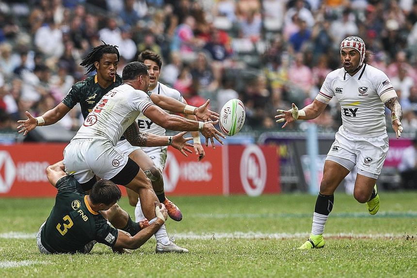 Martin Iosefo passing the ball to a teammate while being tackled by Impi Visser of South Africa yesterday. The US defeated the Blitzboks 21-12 in their Hong Kong Sevens quarter-final but fell 28-19 to eventual champions Fiji in the semi-finals. They