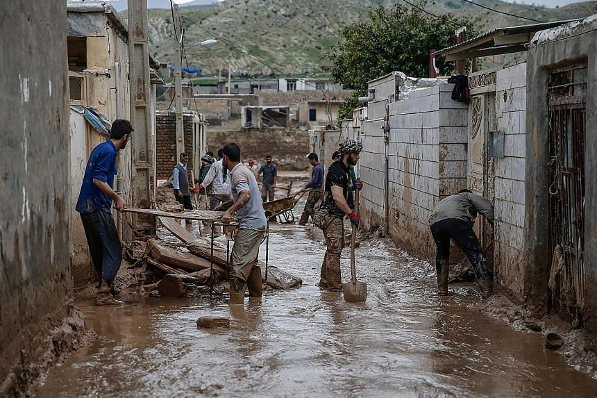 Men clearing away mud yesterday, following floods in the city of Mamulan in Iran's Lorestan province. Thousands have been displaced by flooding in the province.
