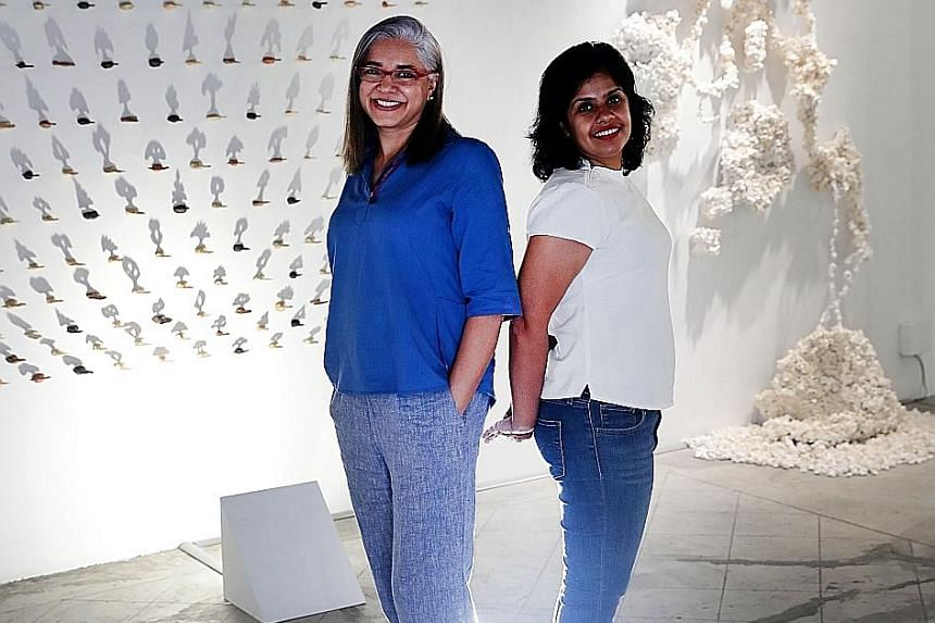 Artists Madhvi Subrahmanian (left), in front of her Forest Of Shadows work, which features 200 small ceramic trees casting their shadows on a wall; and Nandita Mukand, with her Entropic Orders, which is made of paper, wire, resin and adhesives.