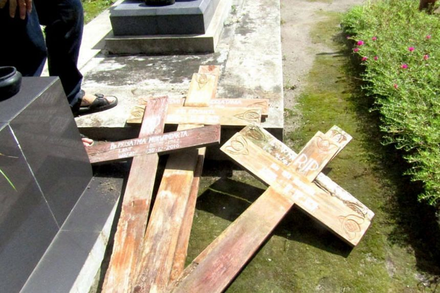 Wooden crosses that were pulled out of their graves are seen at Bethesda Hospital's cemetery in Yogyakarta.
