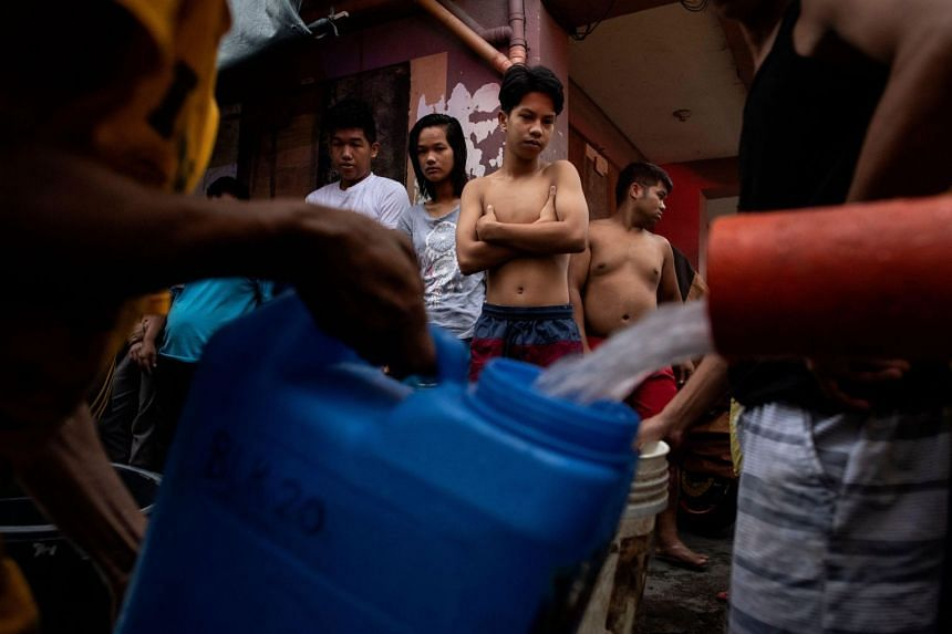 Residents of Addition Hills in Madaluyong City, Manila, queue to receive water distributed from water tank trucks and fire trucks.