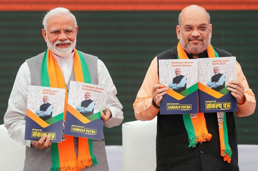 Indian Prime Minister Narendra Modi and chief of India's ruling Bharatiya Janata Party Amit Shah with their party's election manifesto in New Delhi on April 8, 2019.