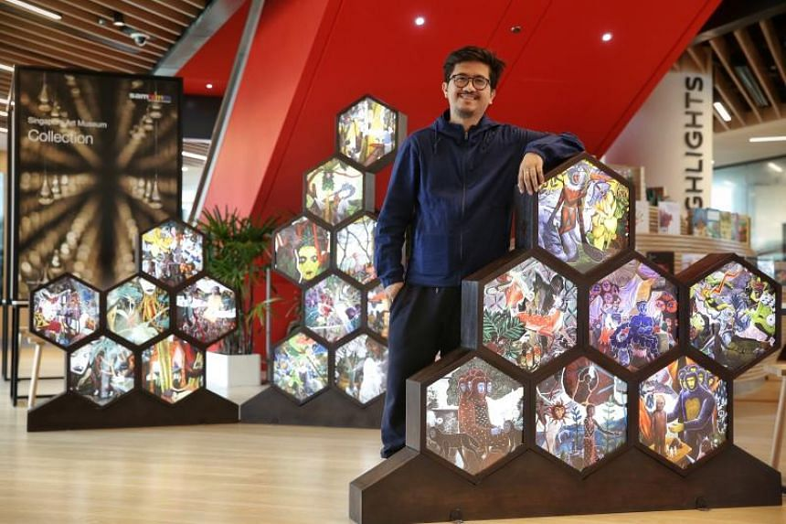 Filipino artist Rodel Tapaya with his hexagonal lightboxes at the SAM Mini Mobile Museum showcase at the Tampines Regional Library.