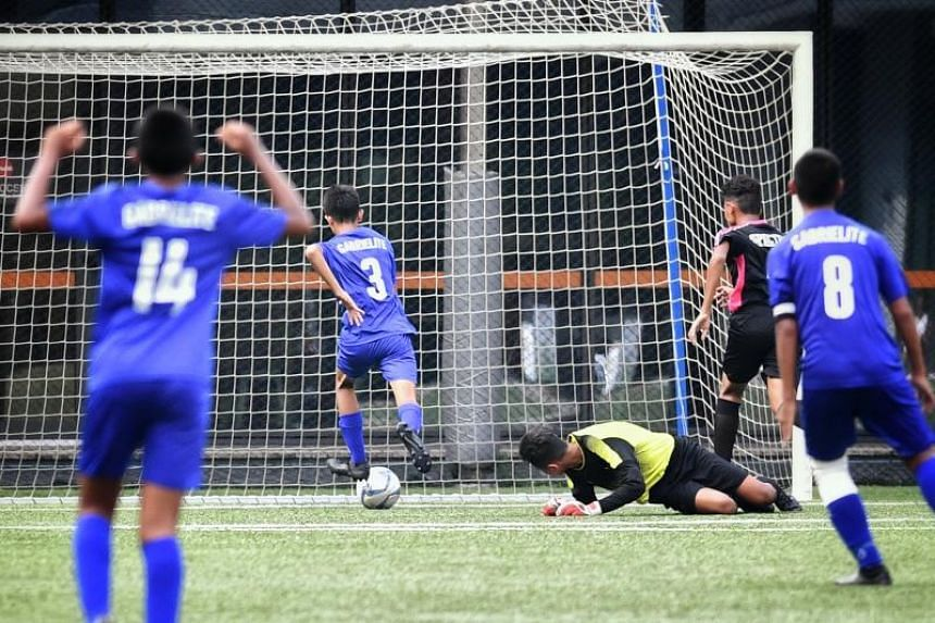 St Gabriel's Aiman Yazid (second left) scores a goal in the B division boys football finals between Spectra Secondary School and St Gabriel's Secondary School at Our Tampines Hub on April 8, 2019.
