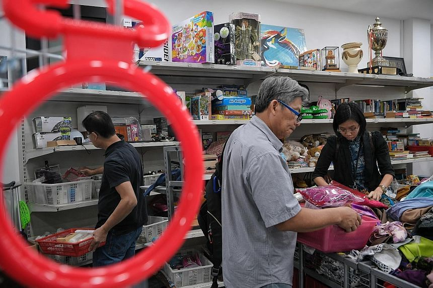 People browsing through goods at Singapore Red Cross' thrift shop, Shop+, which reopened to the public on Jan 2 after a facelift and pulls in between 200 and 300 customers a week. The society stopped collecting public donations in January and now rel