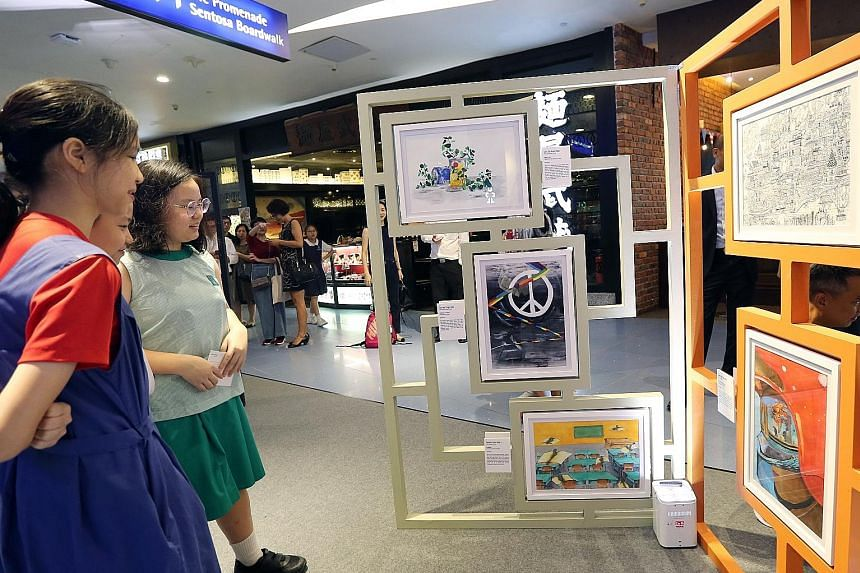 Pupils looking at works on display at the opening of the Top 50 Finalists Exhibition of the School of the Arts (Sota) Primary 6 Art Competition 2019 yesterday, which Education Minister Ong Ye Kung also visited. The annual visual arts competition, now