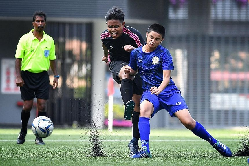 Spectra Secondary School's Muhd Zahin Hidayatullah taking a shot under the challenge of St Gabriel's defender Gideon Tai during the Schools National B Division boys' League Three football final at Our Tampines Hub yesterday. St Gabriel's won 2-0.