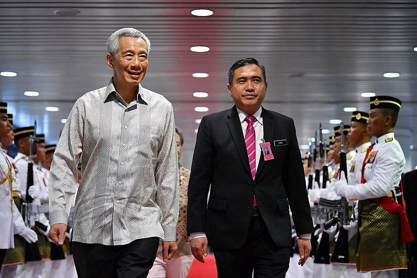 Prime Minister Lee Hsien Loong inspecting a guard of honour on his arrival at Kuala Lumpur International Airport yesterday, accompanied by Malaysian Transport Minister Anthony Loke. This is the first Leaders' Retreat with Malaysia's Pakatan Harapan g