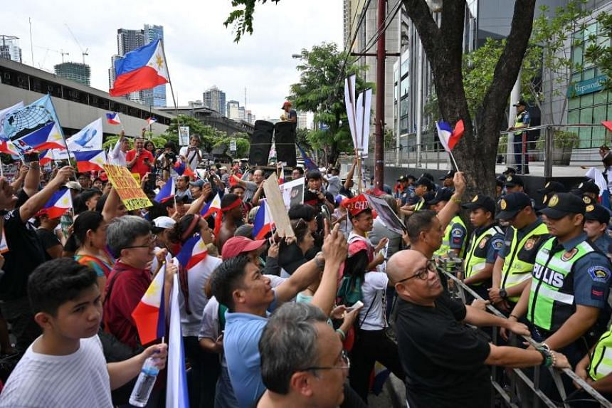 People taking part in a protest in front of the consular office of China, in the financial district of Manila, as policemen stand guard on April 9, 2019.