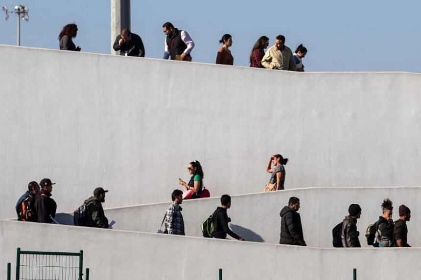 A group of asylum seekers from Central America return to Mexico from the United States, escorted by Mexican migration officers, while their cases are processed by US authorities, at the El Chaparral border crossing on the US-Mexico border, in Tijuana